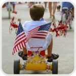 boy riding bicycle in 4th of July parade